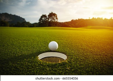 selective focus. white golf ball near hole on green grass good for background with sunlight and lens flare effect