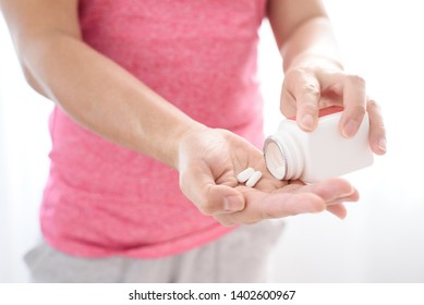 Selective focus at a white pill painkiller from a bottle on woman hand