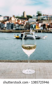 Selective focus of white wine glass overlooking Vila Nova de Gaia embankment at Cais da Ribeira on the River Douro in Porto, Portugal - reflection of bridge on glass