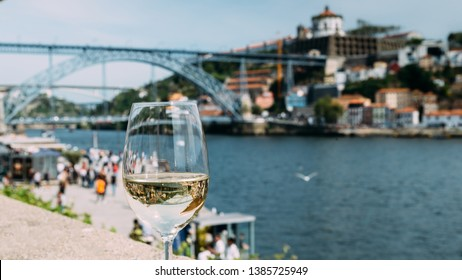 Selective focus of white wine glass overlooking Cais da Ribeira and Ponte de Dom Luis I on the River Douro in Porto, Portugal - reflection of bridge on glass