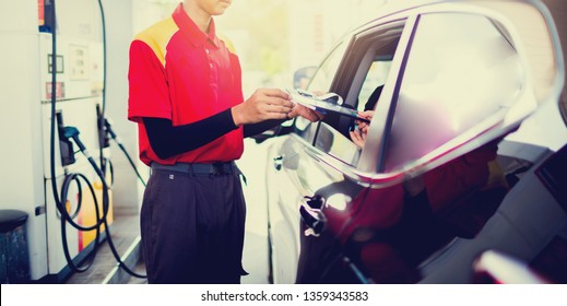 Selective focus to woman driver pay credit card with staff for fuel in gas station.