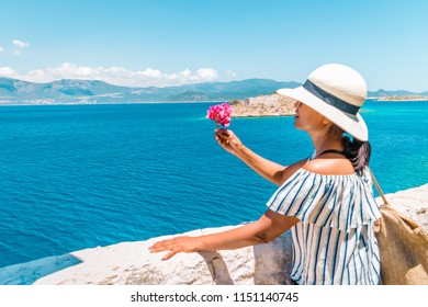 selective focus of woman hand with pink flowers by the ocean, Kastellorizo Island (Megisti,Meis), Greece