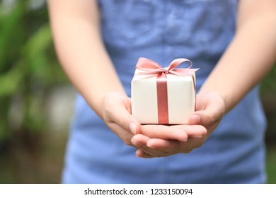Selective focus of Woman hands holding yellow gift box with pink ribbon for Christmas and New Year's Day or Greeting season