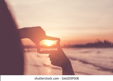 Selective focus of woman hands making frame by finger gesture with sunrise on mountain, Female capture sunrise or sunlight outdoor. Future planning concept.
