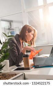 selective focus of woman holding paper plane and looking at laptop near disposable cup in office, procrastination concept