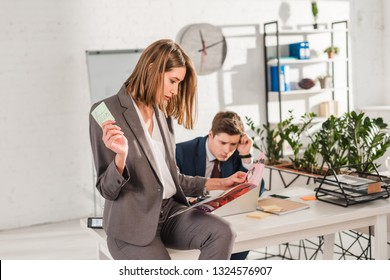 selective focus of woman holding sticky note with later lettering and reading magazine with coworker sitting at desk on background, procrastination concept