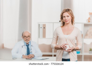 selective focus of woman with medicines in hands with senior doctor sitting at workplace in clinic