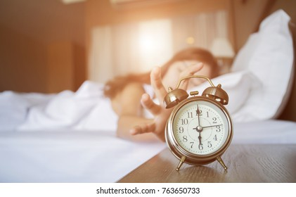Selective focus  woman waking up and turning off the alarm clock. Not enough sleep concept.