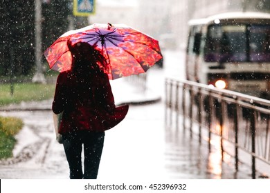 Selective focus. Woman walking with umbrella while raining