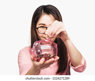 Selective focus woman wearing a pink shirt putting coins in a clear piggy bank,saving concept