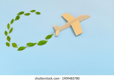 Selective focus of wooden airplane model emitting fresh green leaves on blue background. Sustainable travel; clean and green energy; and biofuel for aviation industry concept.