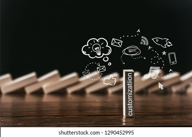selective focus of wooden brick with word 'customization' and icons isolated on black