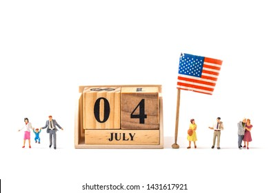 selective focus of wooden calendar and  miniature people , couple , and family  with United State flag isolated on white background, creative image for 4 July independent day celebrate concept.
