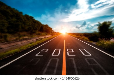 Selective focus word 2020 written on highway road in the middle of Empty asphalt road at golden sunset and beautiful blue sky. vintage tone.