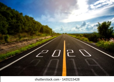 Selective focus word 2020 written on highway road in the middle of Empty asphalt road at golden sunset and beautiful blue sky. Concept new year 2020.