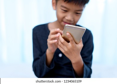 Selective focus at young Asian boy hand using a smartphone to play game with internet connection.