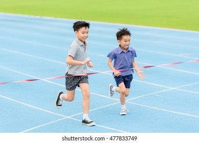 Selective focus at young Asian boy running on blue track to the finished line.