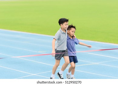 Selective focus at young Asian boy carry each other to finished line.