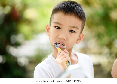 Selective focus at young Asian boy brushing his teeth in the home garden with out focus green plant background.