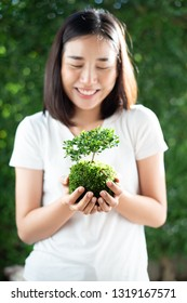Selective focus at young Asian Thai woman carry little seeling plant. Earth day concept.