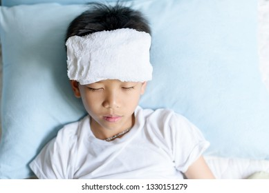 Selective focus at young Asian Thai boy sick and take rest and sleep on a bed in.
