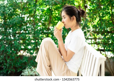 Selective focus at young Asian Thai woman drink a coffee in home garden with green plant background.