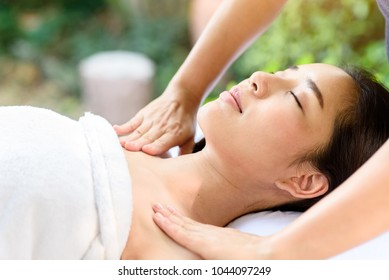 Selective focus at Young Asian woman face feel relax during body and sholder massage at garden in spa resort.