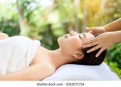Selective focus at Young Asian woman face feel relax during oil massage at garden in spa resort.