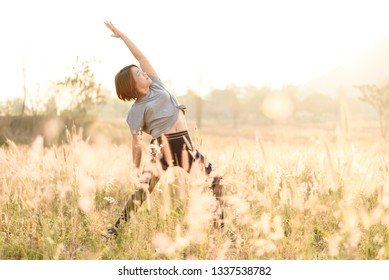 Selective focus of young Asian woman do yoga on a field during the moring under the golden sunligh.