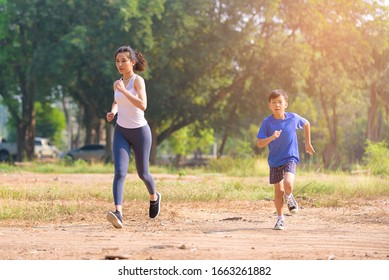 Selective focus at young Asian woman and boy running with happy in a park during summer day in a morning.