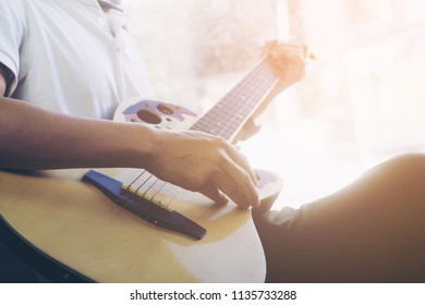 Selective focus Young man sitting on the window playing the guitar at home