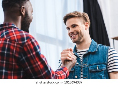 selective focus of young multiethnic men smiling each other