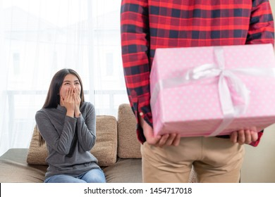 Selective focus young pretty woman sitting on couch with feeling exciting while waiting present from boyfriend, young man holding gift box behind his back