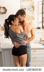 selective focus of young seductive couple passionately hugging in kitchen