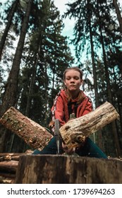 Selective focus. Young strong girl teenager chopping wood with axe blow in forest. Purposeful ambitious teen with male character. Camping and wild travel. Lumberjack woman cuts firewood for bonfire