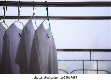 Selective Focused white T Shirts on Cloth hangers at the balcony of residential building in a rainy day with blurry city view background, cannot dry clothes on bad day. City Life, Living on High Rise