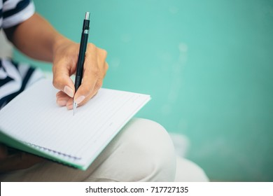 selective focus.hand of high school or university student in casual uniform holding pencil writing on paper note book on blue pastel background.concept for education.