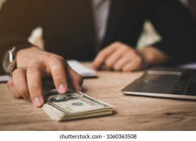 Selective focus,Man offering batch of hundred dollar bills. Hands close up. Venality, bribe, corruption concept. Hand giving money - United States Dollars (or USD),filter color effect.