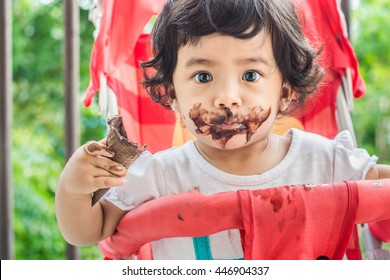 Selective focus,Soft focus Cute Toddler Girl with Mouth Smeared with Chocolate.