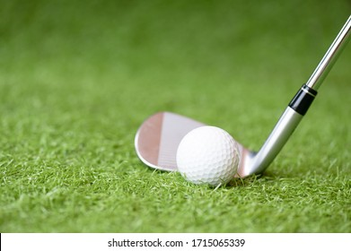 Selective golf club and golf ball on green grass background.Iron golf club hitting ball into a hole.Outdoor sport.