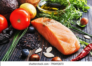 Selective of ingredients with fish and organic vegetables, cereals rich of amino acids,  oligominerals  for healthy seasonal cooking on black wooden background, top view, place for text.