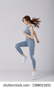 Selective motion focus of Asian girl wear exercise suit pose running in studio