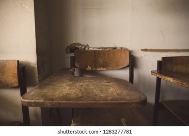selective soft and blur focus.old wooden row lecture chairs in dirty classroom in poor school.study room without student.concept for education in third world ,donate and charity,background text