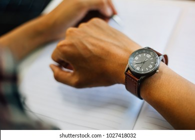 selective soft focus businessman looking at his watch on his hand, watching the time and writing something on note book at work space on table