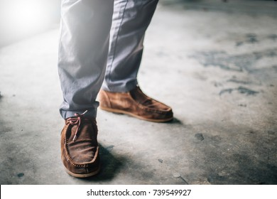 selective soft focus hipster wear old boots on yellow pastel color wall background. with copy space for text.stylish and fashion men shoes concept.vintage tone