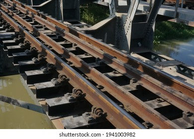Selective and soft focus structure railway of steel bridge crossing river in Thailand, sunlight shines on objects. Concept of structure, structure steel, railway, crossing river.