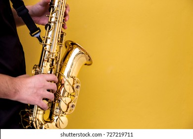 selective soft focus.hands saxophonist playing saxophone on yellow pastel wall background.concept for instrument musician,world Jazz festival,musical background.copy space for text.
