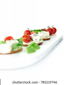 Selectively focused feta cheese, basil and tomato canapes shot against a bright, white background with generous accommodation for copy space.