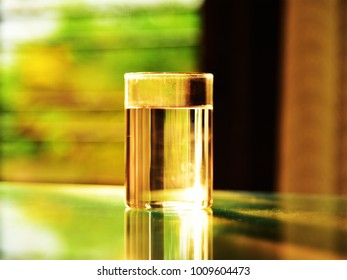 A selectively focused glass of water on a glass table against the golden morning sunlight.