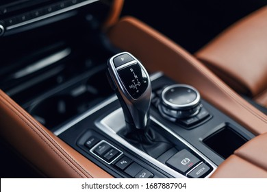 Selector automatic transmission with leather in the interior of a modern expensive car. The background is blurred. Black and brown leather car interior. Luxurious car instrument cluster. Close up shot